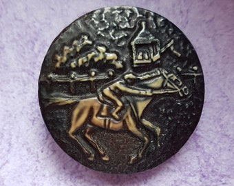A vintage 1930s textured celluloid 'Racehorse and Rider' button in dark green and cream. 3.2 cms.