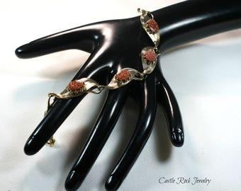 Stunning gold flecked and brown sparkling Goldstone bracelet set in a gold leaf pattern.