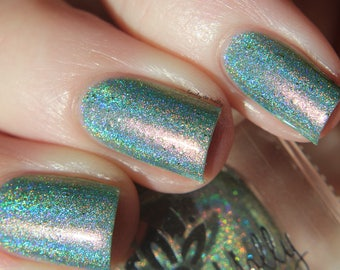 "Nail polish - ""Strangeness And Charm"" A light green holo with gold flakes and pink to gold shifting shimmer."