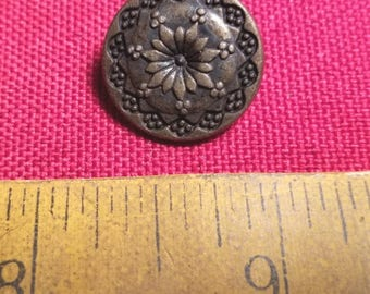 Single shanked button in a floral pattern with an antique copper finish