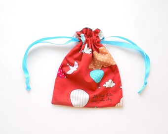 Small reversible drawstring pouch, storage bag or gift bag with hot air balloons on a red background; and solid turquoise on reverse
