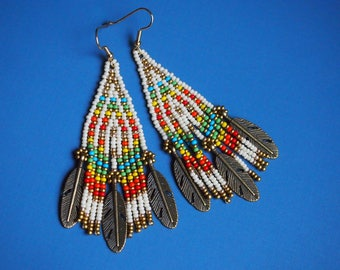 brass feather charm and rainbow seed bead fringe earrings. boho feather beaded earrings. brass fringe earrings. rainbow and bronze