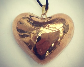 Large gold heart pendant on an adjustable leather thong.