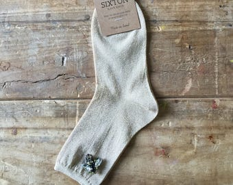 Monaco socks in sand and a bee pin