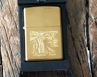 Brand new in box collectible brass Zippo cigarette lighter with an etched picture of Niagara Falls on the front