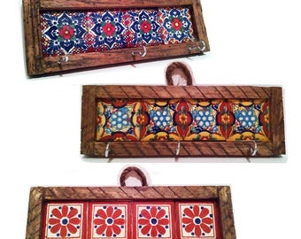 Wooden and ceramic key holder with floral design.