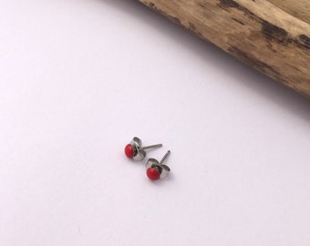 New improved waterproof design! Itty bitty, cherry red, eco-resin studs on allergy-friendly surgical steel.