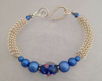 Silver wirework bracelet, with blue floral lampwork focal bead.
