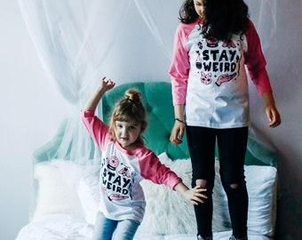 Stay Weird Solid White/Pink Raglan Kids T-Shirt. 3/4 length baseball child tee. Spooky, magic shirt for Boys and Girls