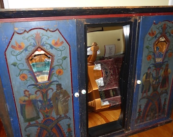 Large Hungarian cabinet with eyeball knobs and fun house mirror