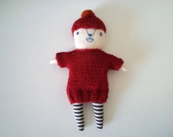 a doll wearing burgundy knits