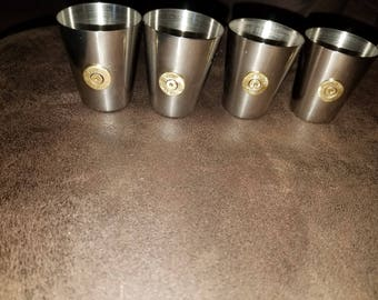 Set of 4 stainless steel shot glasses. .45 cal casing in the center of each one.