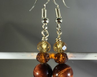 Brownish red cat's eye 8mm bead with brown and yellow crystals. French Hook.
