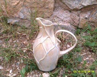 white ceramic pottery pitcher with crystalline glaze and raised pattern