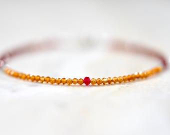 thin garnet beaded bracelet. golden hessonite garnet beaded bracelet with ruby and amazonite detail. thin garnet string bracelet.
