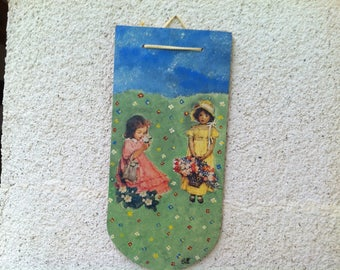 Wooden tile(blow) representing girls in the meadow