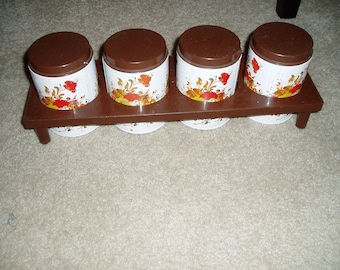 Four Small Metal Canisters With Plastic Lids