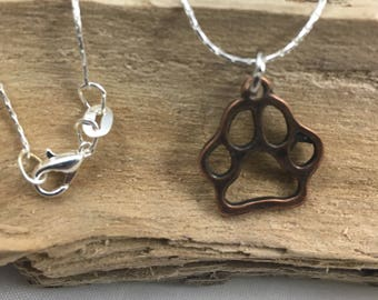 Necklace. Silver beaded necklace with bronze paw print charm