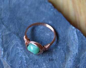 Copper wire wrapped ring with blue-green glass bead