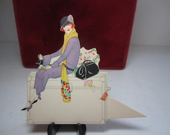 Art deco 1920's die cut unused place card pretty deco lady sitting on her steamer in fashionable dress and cloche hat carry on bag and purse