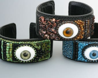 Bead embroidered cuff bracelet. Eye bracelet. Glass eyes. Three colors. Leather embellished with glass doll eyes and beads, sequins, pearls.