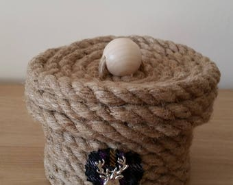 Hand sewn round rope storage container with lid and tartan motif with stags head emblem.