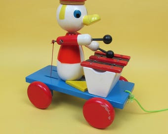 Vintage wooden duck pull-along. Duck playing a glockenspiel as he trundles along. Very cute!