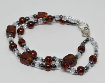 Lovely silver tone metal and red beads bracelet