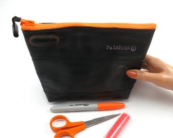 Recycled bicycle inner tube cosmetic pouch for men and woman, container, bag, with neon orange zipper.