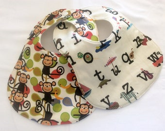 Set of two hand-made baby bibs with monkey and alphabet print fabric