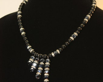 Black glass pearls and black crystal beads with fours graduated pendants. A stunning set of necklace, bracelet and earrings.