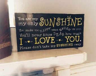You are my Sunshine sign done in black, white and yellow and also on stained wood. Hand painted stenciled hung with sawtooth hanger. 10x18
