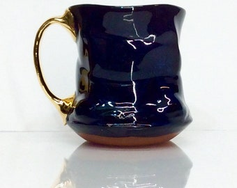 black mug with ocean spray rutile and four finger gold handle