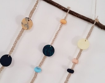 Macrame wall hanging featuring multi-coloured clay beads