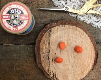 Tiny round vintage orange buttons