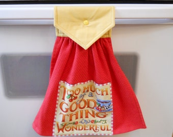 Hanging red kitchen towel with panel on the front.  Too much of a good thing is wonderful.