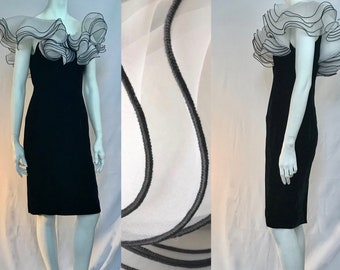 A cloud of ruffles at the neckline - in tiers - is a dramatic and sassy topping for the sleek and slim black velvet dress.