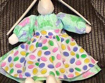 lapin en peluche à la main avec robe de Pâques et tablier, lapin de Pâques