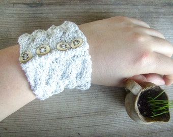 Knitted cuff in white and silver with metallic buttons. Slip on bracelet