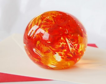 Glass paperweight in oranges