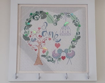 "Birds and heart original cross stitch design with sequin detailing and the word ""Love"" in a white framed picture with hooks"