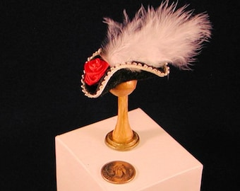 Miniature cavalier tricorn black felt hat, ivory braid trim, white feather plume, scarlet red ribbon rose. 1 to 12  scale. Handmade in USA.