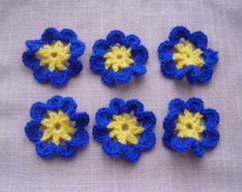 6 flowers are hand crocheted in blue and yellow wool