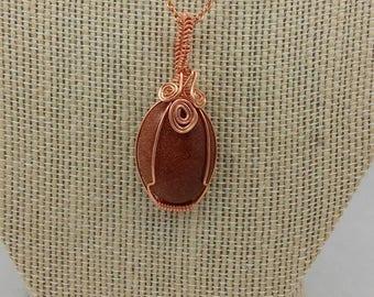 Goldstone cabochon wrapped in copper wire