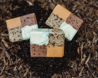 Scrubby Exfoliating soap with avocado oil, coffee grounds, walnut shells, patchouli, mint and Mandarin.