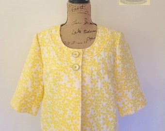 Vintage white and yellow daisy print jacket w/ scoop neckline, half sleeves and front button enclosure. By Alfani. Size Large