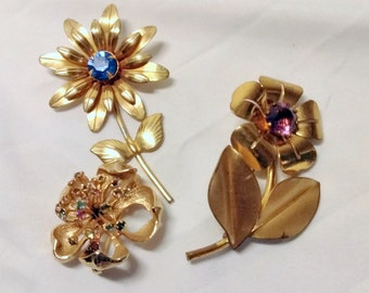 Three vintage gold tone flower brooches unsigned