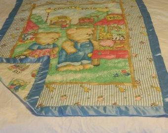 This baby blanket shows the Teddy Bear family at the County Fair. BB9
