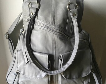 Tan leather shoulder tote and backpack in one. Stylish and functional. Convertible rucksack and backpack.Lined with pockets,rolled handles