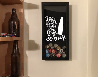 """Bottle Cap Holder Shadow Box - This Home Runs on Love & Beer - Black (6"""" x 14"""") - Vinyl Decal Gifts, Home Bar Accessories"""
